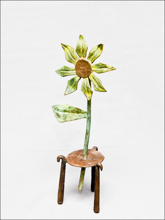 Figuras de bronce. Flor amarilla sobre bastoncillos.