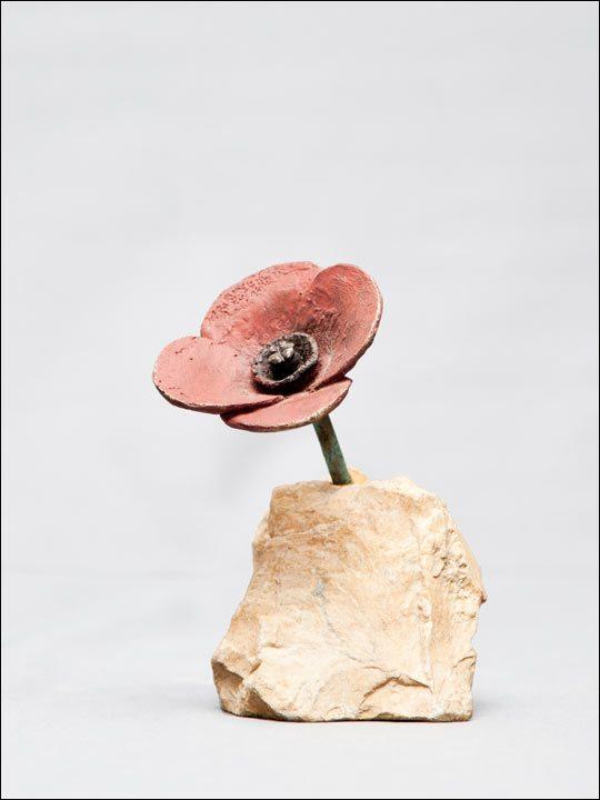 Flor de bronce en piedra. Amapola.