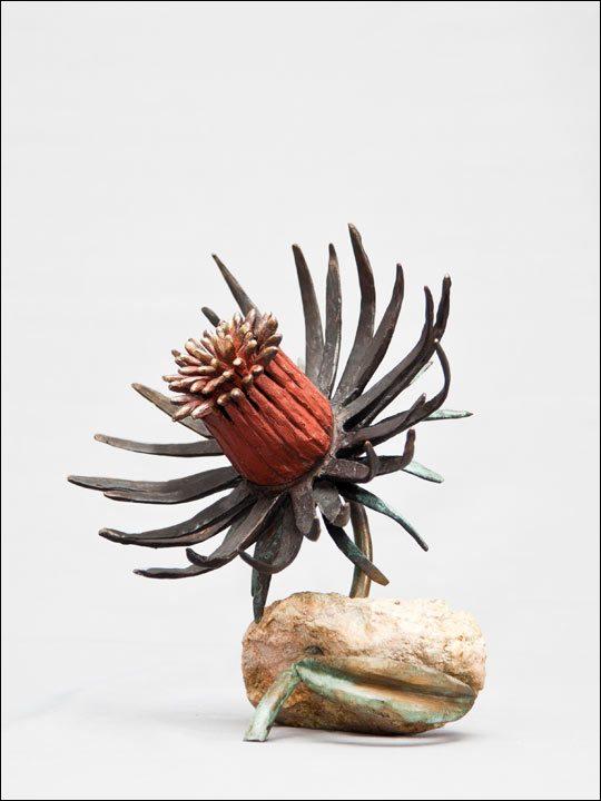 Figura de bronce. Flor roja en piedra.